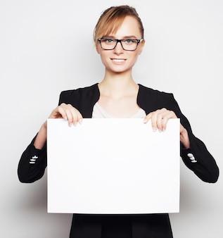 Концепция бизнеса, финансов и людей: портрет красивой деловой женщины, держащей пустой рекламный щит. готов добавить текст. на сером фоне.