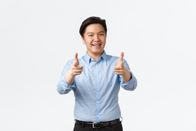 ビジネス、金融、人の概念。親指を立てて歯ブレースを見せて満足しているアジアのビジネスマン、サラリーマンは製品をお勧めするか、良い仕事を褒め、白い背景