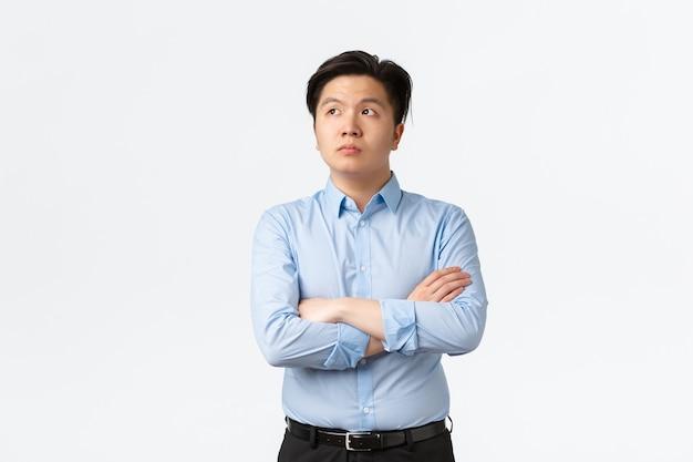 ビジネス、金融、人の概念。青いシャツを着た思いやりのあるアジアのビジネスマン、腕を組んで左上隅を見て、選択をし、考えたり、空想にふけったり、白い壁に立ったりします。