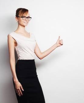 Концепция бизнеса, финансов и людей: молодая деловая женщина что-то показывает на сером фоне