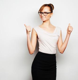 Концепция бизнеса, финансов и людей: молодая бизнес-леди в очках. на сером фоне.