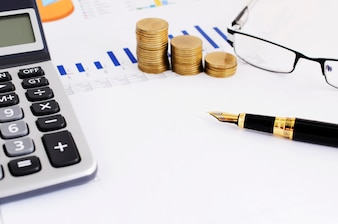 Business Finance concept with close up of fountain pen and coins stack