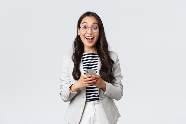 Business, finance and employment, female successful entrepreneurs concept. cheerful happy asian businesswoman, office manager looking upbeat camera with smile, using smartphone