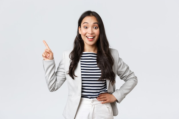 Business, finance and employment, female successful entrepreneurs concept. cheerful successful businesswoman in white suit pointing fingers upper left corner, showing advertisement.
