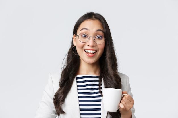 Affari, finanza e occupazione, concetto di imprenditrici di successo. primo piano di un impiegato asiatico sorridente uscente che parla con un collega alla cucina dell'ufficio, bevendo caffè