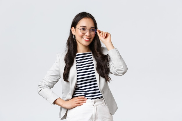 Business, finance and employment, female successful entrepreneurs concept. confident businesswoman in glasses and white suit ready for meeting, smiling pleased, standing determined