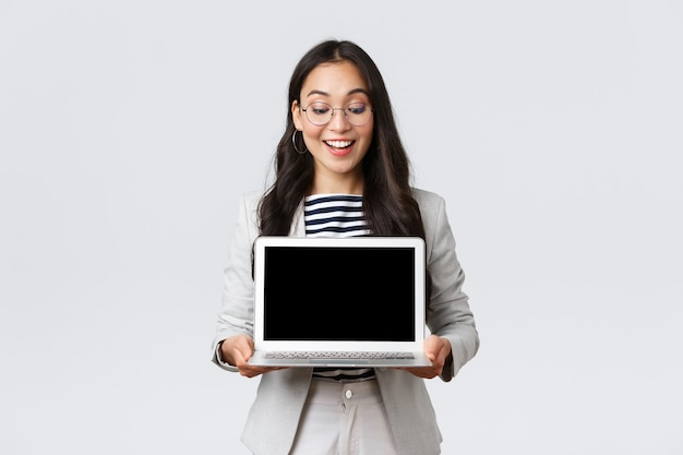 Business, finance and employment, female successful entrepreneurs concept. enthusiastic businesswoman in suit and glasses showing presentation, demonstrate her project on laptop screen