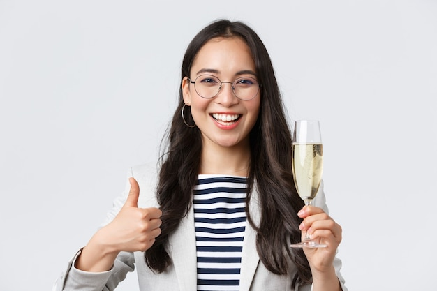 Business, finance and employment, female successful entrepreneurs concept. happy asian businesswoman celebrating, having office party, drinking champagne and show thumbs-up