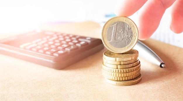 ビジネス、金融または投資の概念。コイン、小切手帳またはメモ帳、万年筆、電卓。