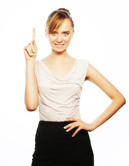 Business, finance and people concept:  young business woman pointing at white background.