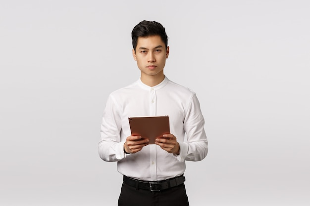 Business, finance and recruitment concept. handsome elegant young asian man holding digital tablet and looking serious, being busy, control work remote, hr interviewing applicants