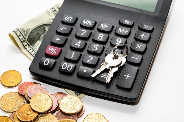 비즈니스, 금융, 돈 또는 자동차 대출 개념을 저장합니다. 키, 동전 스택, 책상 테이블에 계산기