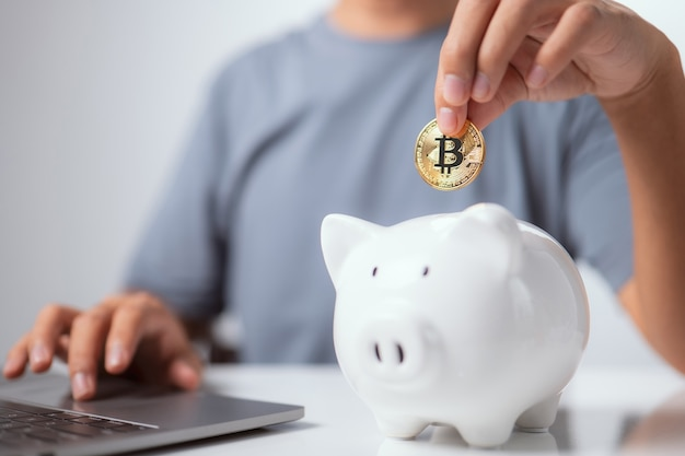 Business and finance savings man is putting golden cryptocurrency bitcoin in white piggy bank