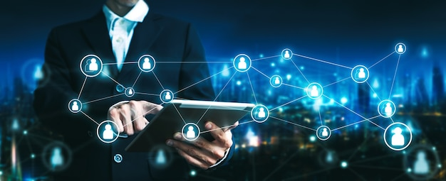 Business finance and smart city technology concept, professional business man using digital tablet with futuristic interface graphic of people network on future city background at night in bangkok