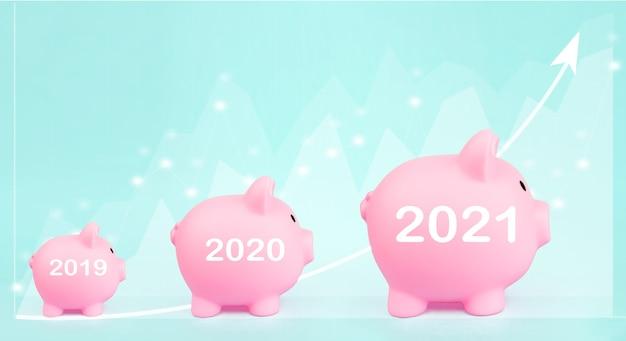 仕事。ファイナンス。富。青い背景に2021年に成長している収益を示すデジタルホログラム財務チャートを備えた3つのピンクの貯金箱。