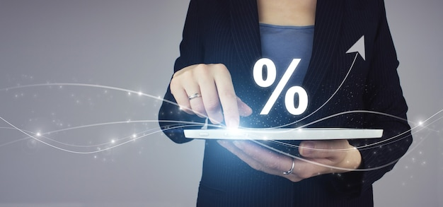 Business. finance. wealth. white tablet in businesswoman hand with didgital hologram interest rate and arrow on grey background. successful international financial investment concept.