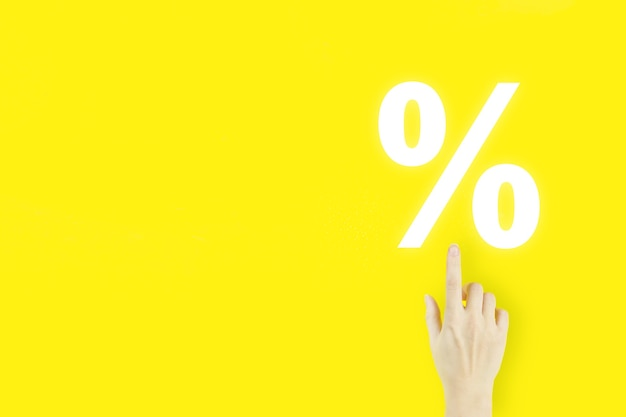 Business. finance. wealth. young woman's hand pointing finger with hologram interest rate on yellow background. successful international financial investment concept.
