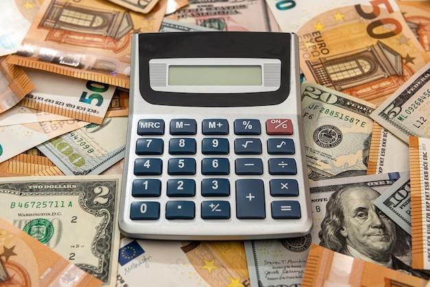 机の上に計算機を備えたビジネス財務会計のドル紙幣とユーロ紙幣