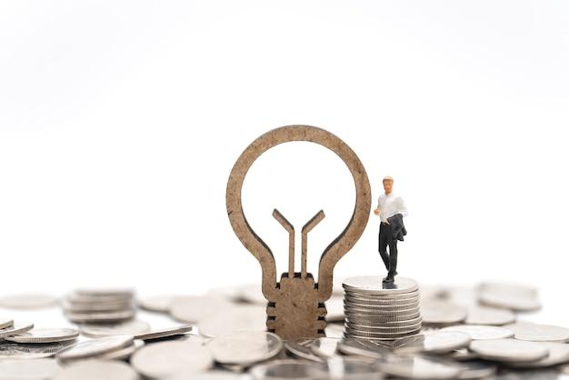 비즈니스, 금융 및 아이디어 개념입니다. 흰색 바탕에 나무 전구 아이콘이 있는 은화 더미에 서 있는 사업가 미니어처 그림 사람들.