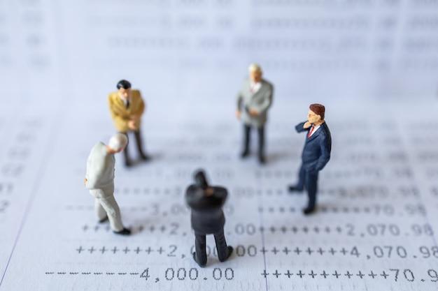 ビジネス財務とチームワークの概念。ビジネスマンのミニチュアのグループは、銀行通帳に立っている人々を示しています。