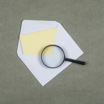 Business and financial concept with letter in envelope, magnifying glass on grey surface flat lay.