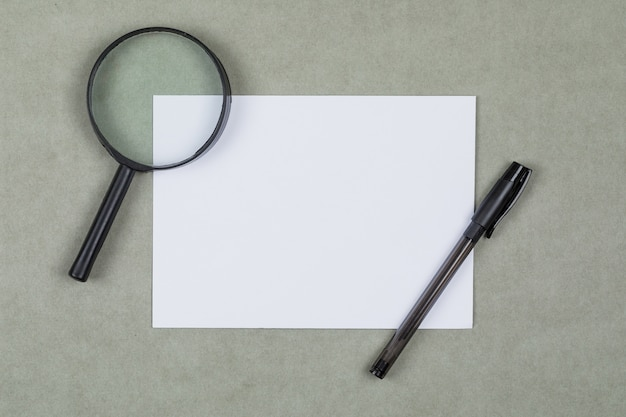 Business and financial concept with magnifying glass, pen, blank paper on grey background flat lay.