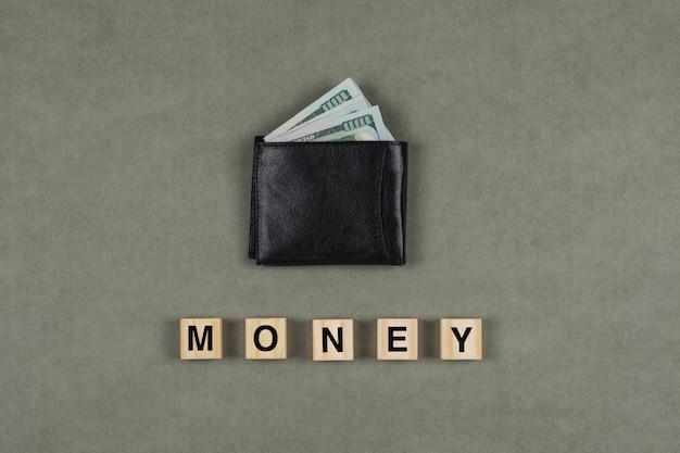 Business and financial concept with money in wallet, wooden cubes on grey surface flat lay.