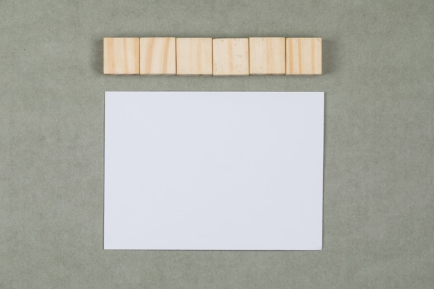 Business and financial concept with wooden cubes, blank paper on grey background flat lay.