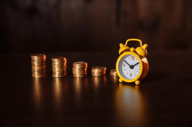 Бизнес-концепция финансовых идей с стопкой монет и будильником на деревянных фоне.