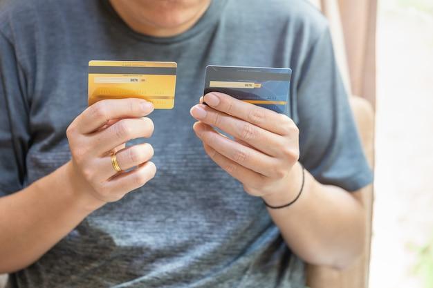 비즈니스, 금융, 지불 및 기술 개념입니다. 두 개의 가짜 신용 카드를 들고 있는 아시아 남자.
