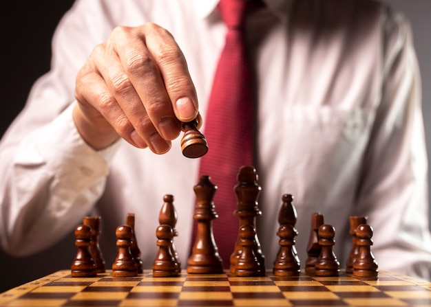 Business financial strategy concept. businessman making decision and moving chess piece over other chess figures.