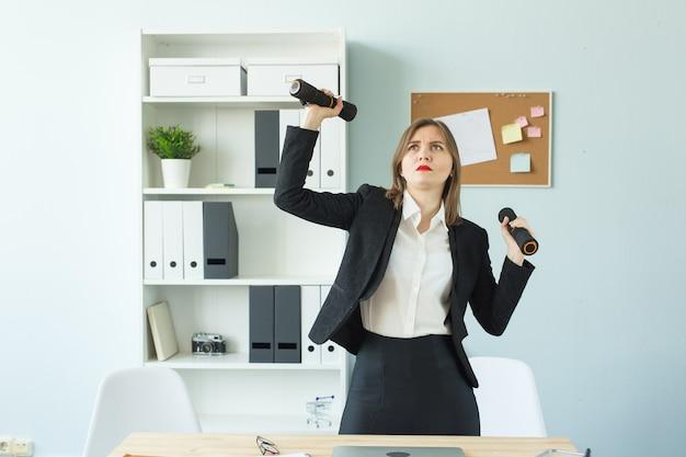 ビジネスフィットネスの人々は彼女のオフィスで働いてスポーツをしている疲れたビジネス女性を概念します
