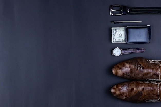 Business flat lay background with a copy space. male shoes, wrist watch wallet,  belt, mobile phone and a necktie on black  background.