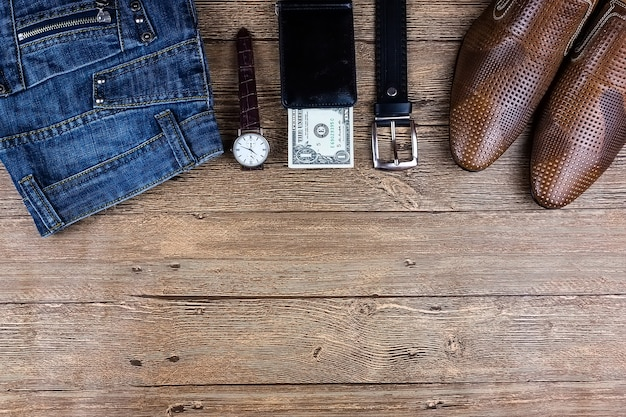 Business flat lay background with a copy space. male shoes, wrist watch, wallet, belt and a necktie on wooden background.