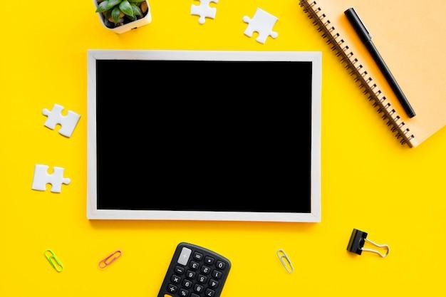 ビジネスフラットは、黄色の背景に黒板、ペン、ジグソーパズルを置く