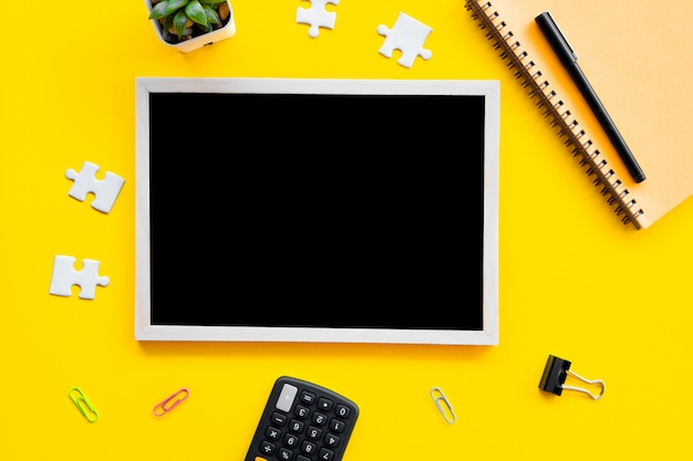 Business flat lay with blackboard ,pen,jigsaw on yellow background