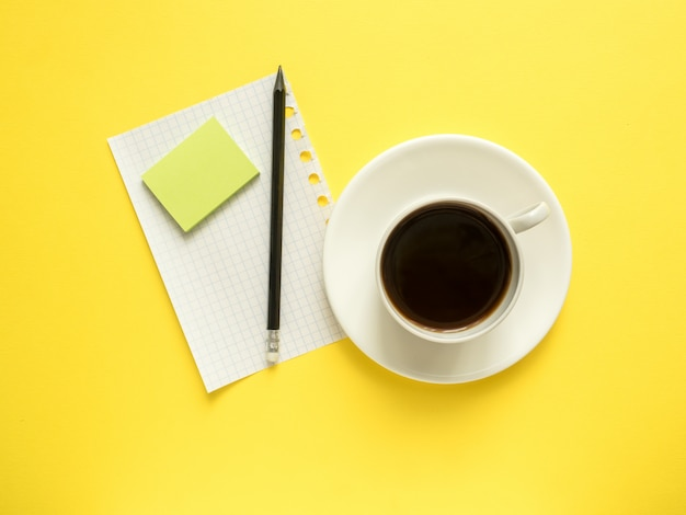Business flat lay with copy space, calculator, pencil, notepad, coffee glasses on colorful yellow background.