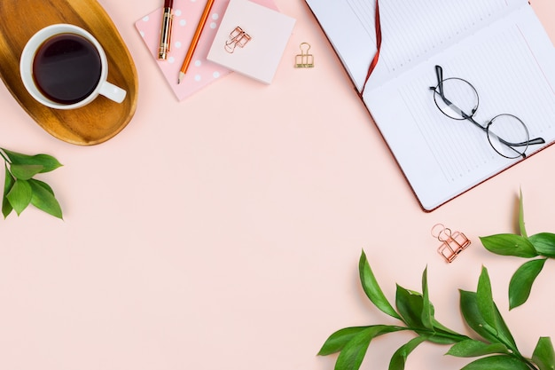 Business flatlay mockup with cup of coffee on a wooden tray, opened notebook, glasses, ruscus branches and other accessories on pastel background with copyspace
