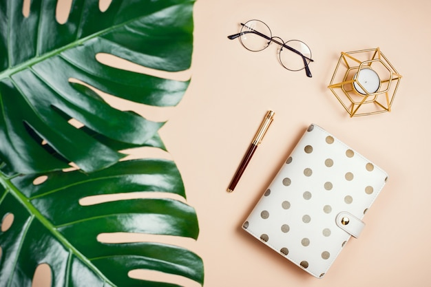 Business flatlay mockup with philodendron monstera leaves, planner, candle and glasses