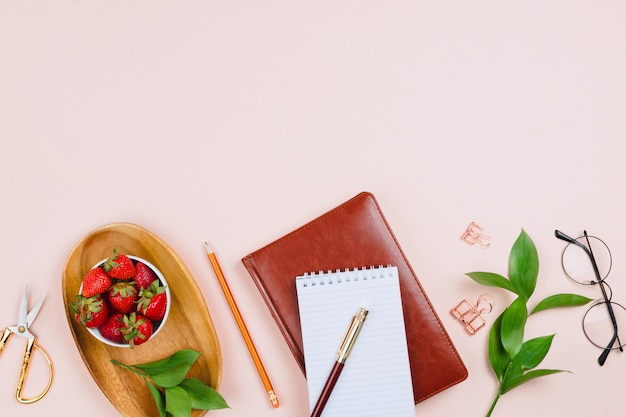 Business flatlay mockup with strawberries on a wooden tray, notebooks, glasses, ruscus branches and other accessories on pastel background with copyspace