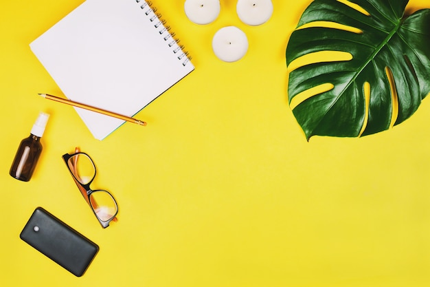 Business flatlay with mobile phone, glasses, philodendron leaf and other accessories. yellow background.