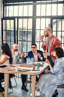 비즈니스, 음식, 점심, 그리고 사람들의 개념 - 행복한 국제 비즈니스 팀이 사무실에서 피자를 먹고 있습니다. 사무실 팀의 외부인.