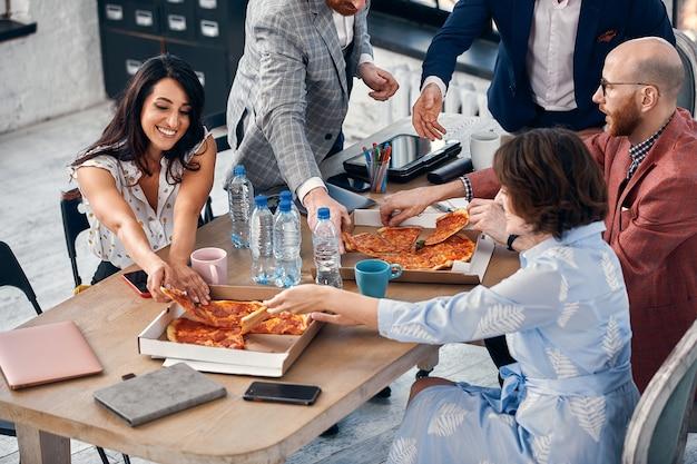 ビジネス、食べ物、昼食、そして人々のコンセプト-オフィスでピザを食べる幸せな国際ビジネスチーム。