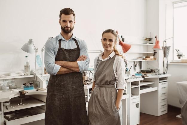 カップルのためのビジネス。ジュエリーワークショップに立ってカメラを見ているエプロンで笑顔のカップルの肖像画。ジュエリー作りのプロセス。仕事。ジュエリーワークショップ。