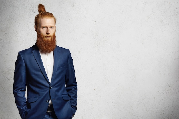 Business, formal style and fashion. good-looking redhead bearded entrepreneur with stylish hair bun dressed in blue elegant suit posing indoors, holding his hands in pockets.
