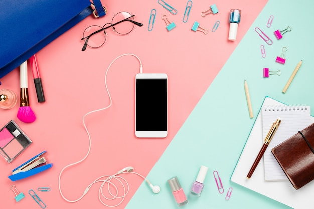 Business frame with woman's blue bag, glasses, smartphone, cosmetics and stationery supples.