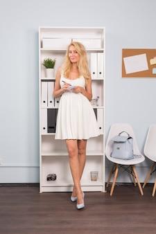 비즈니스, 프리랜서 및 사람 개념 - 메모장을 들고 하얀 드레스를 입은 아름다운 여성의 초상화를 클로즈업
