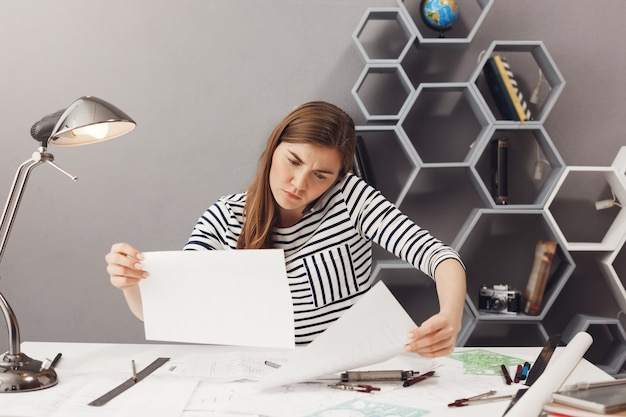 Business, freelance, teamwork concept. young good-looking confused female architect sitting in coworking place, talking on phone with customer, trying to find information in papers.