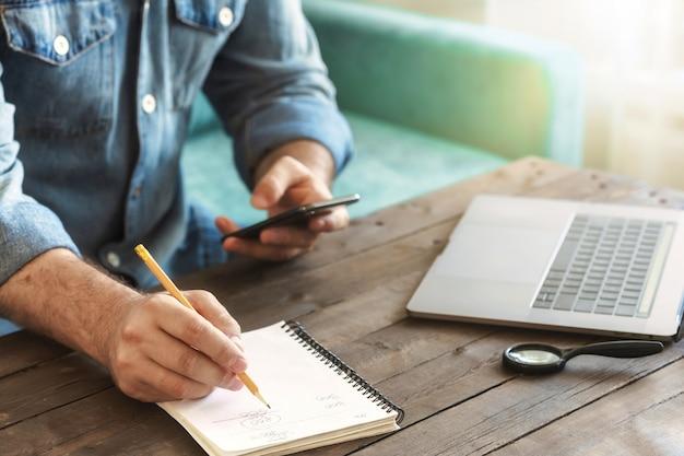 スマートフォンとラップトップで自宅で働くビジネスフリーランサーの男。木製のテーブルの上のノートに書いている男の手書きを閉じます。リモートワークのコンセプト