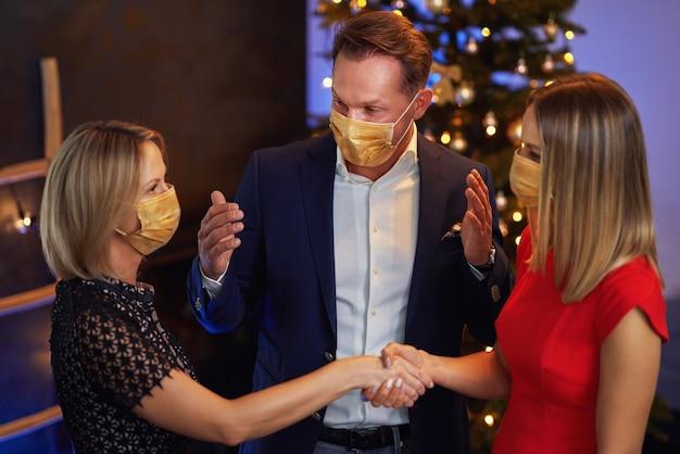 マスクを身に着けているクリスマスパーティーを祝うビジネスの友人。高品質の写真
